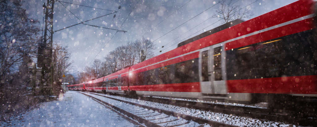 red train speeding in the snow